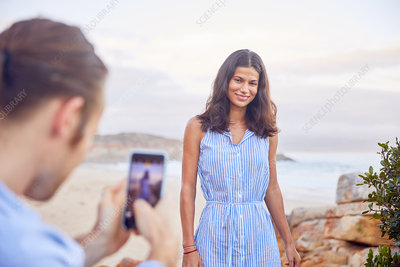 Young man photographing girlfriend at beach