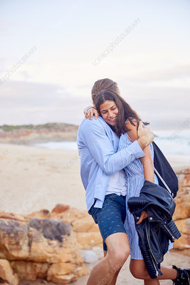 Affectionate couple hugging at beach