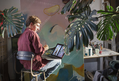 Male artist painting and using laptop
