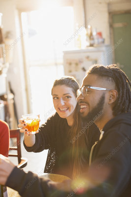 Happy young couple enjoying cocktails