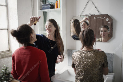 Young women friends getting ready, applying makeup