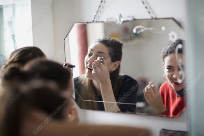 Young women friends applying makeup