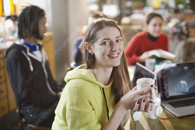 Young woman drinking coffee with roommates