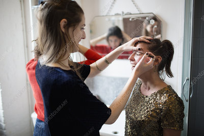 Young women getting ready, applying makeup