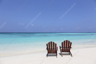 Two adirondack chairs on beach