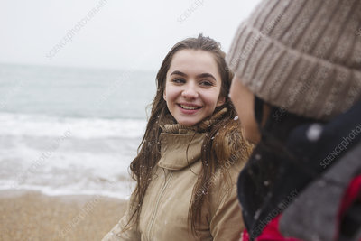 Mother and daughter walking on snowy winter beach