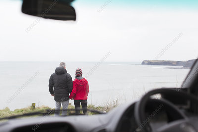 Couple looking at ocean view outside car
