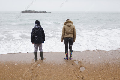 Brother and sister standing on snowy winter beach