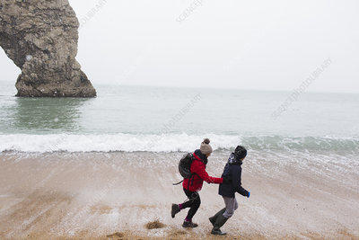 Mother and son running on snowy winter beach