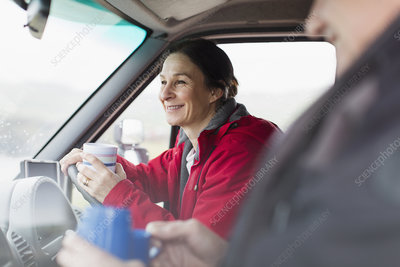 Woman drinking coffee and driving motor home