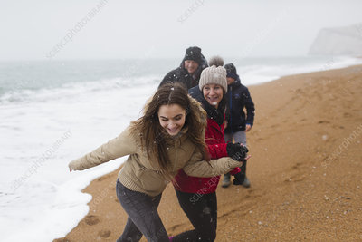 Happy, carefree family on snowy winter beach