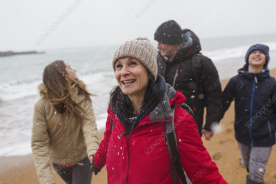Snow falling over happy family on winter beach