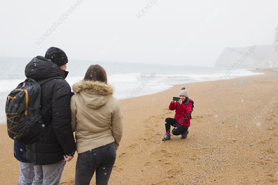 Woman photographing husband and daughter on beach