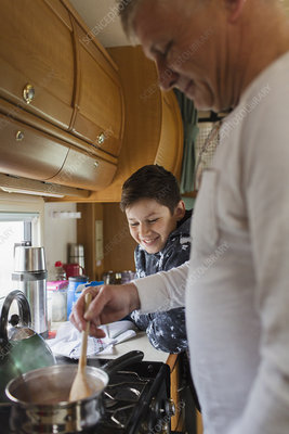Father and son cooking in motor home