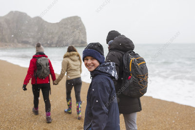 Boy walking on snowy beach with family