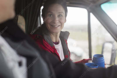 Smiling woman drinking coffee in motor home