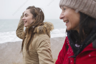 Happy mother and daughter walking on snowy beach