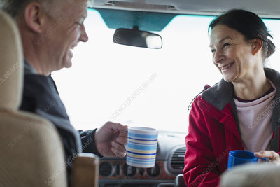 Happy couple drinking coffee in motor home