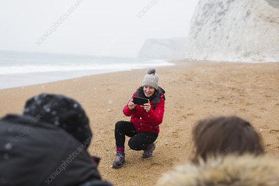 Mother photographing kids on snowy winter beach