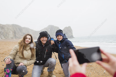 Happy family posing for photograph on beach