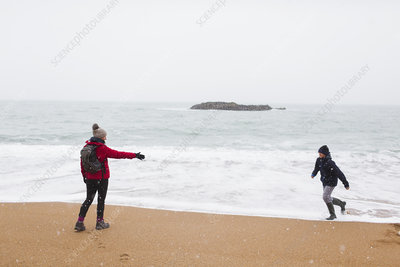 Playful mother and son on snowy winter ocean beach