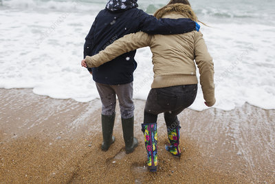 Brother and sister playing in winter ocean surf