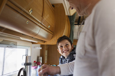 Happy father and son cooking in motor home