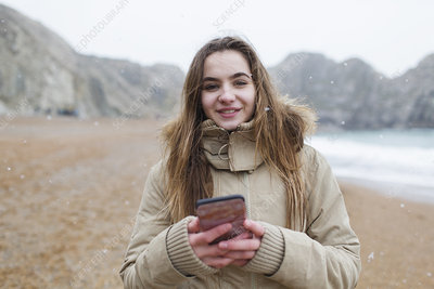 Portrait girl texting with smart phone on beach