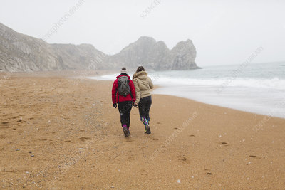 Mother and daughter walking on snowy beach