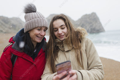 Mother and daughter using smart phone on beach