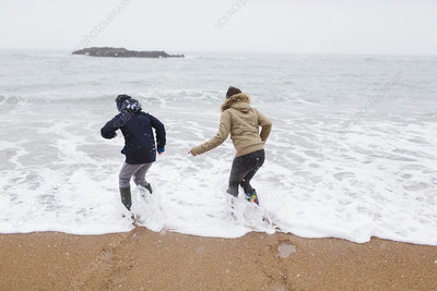 Brother and daughter playing in winter ocean surf