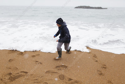 Playful boy playing in winter ocean surf