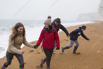 Family in warm clothing on snowy winter beach