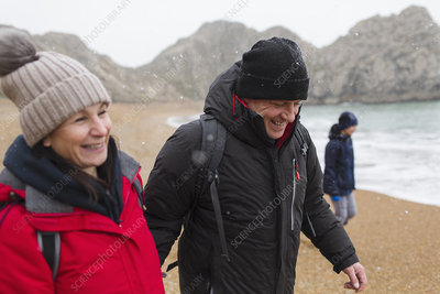 Smiling couple on snowy winter beach