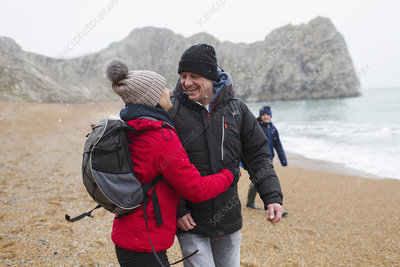 Couple in warm clothing on snowy winter beach