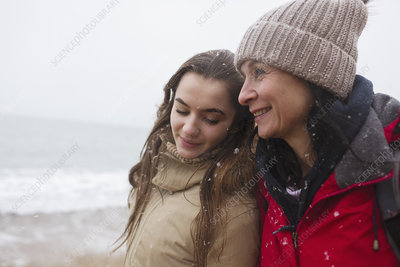 Mother and daughter on snowy winter beach