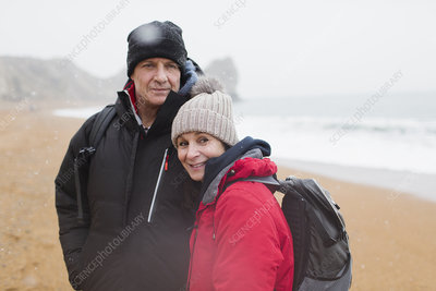 Portrait couple in warm clothing on winter beach