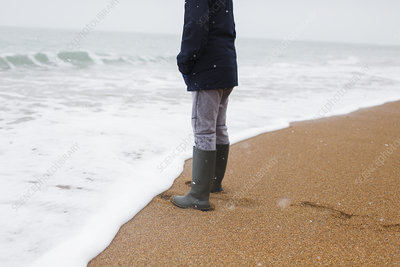 Boy in rubber boots standing on winter beach