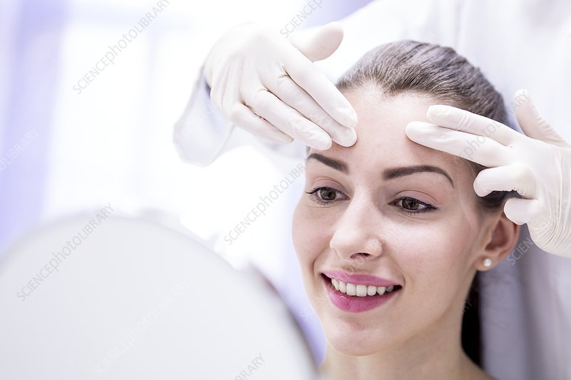 Doctor examining young woman's forehead