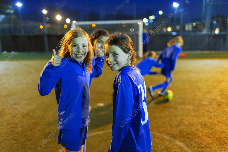 Portrait girl playing soccer, gesturing thumbs-up