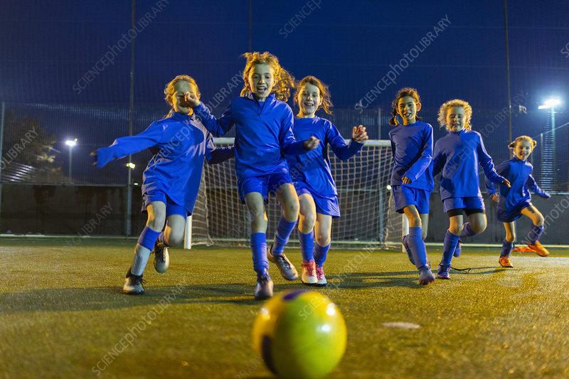 Girls soccer team playing, running toward ball
