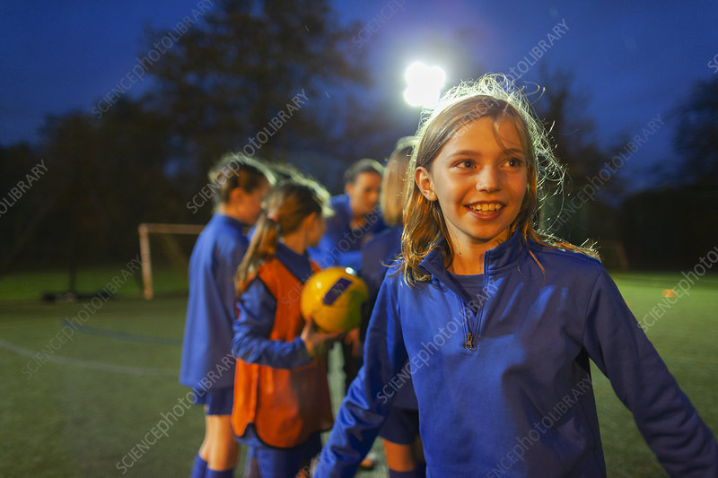 Smiling girl playing soccer