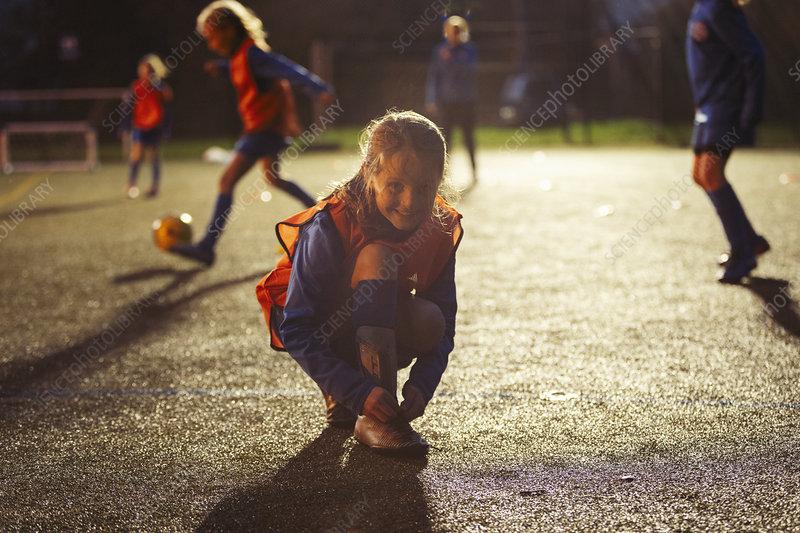 Portrait smiling girl soccer player tying shoe