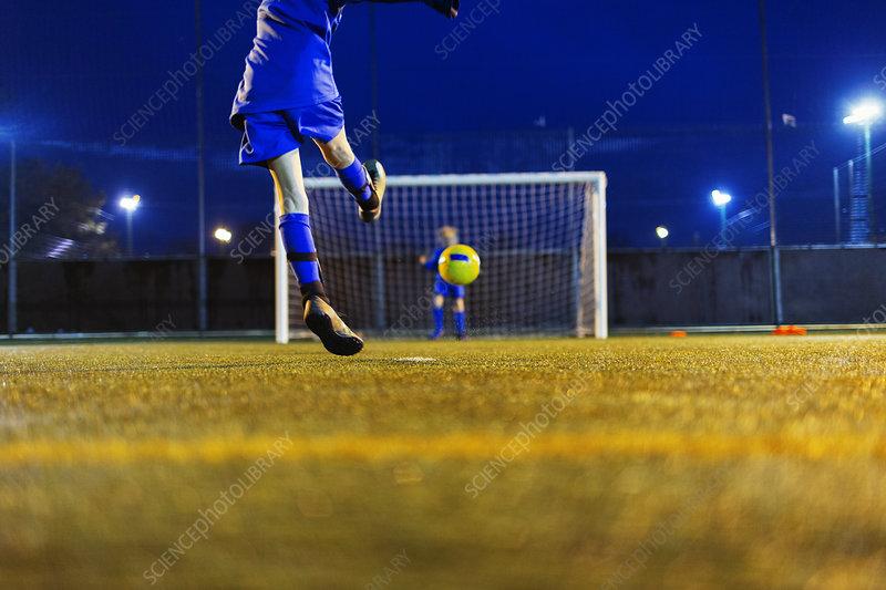 Girl soccer player kicking ball toward goal