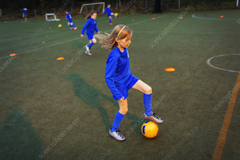 Girl practicing soccer drill