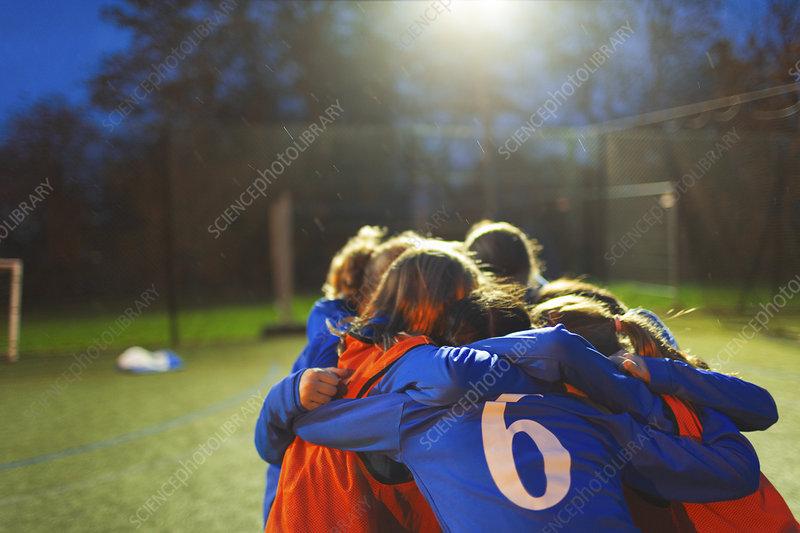 Girls soccer team huddling
