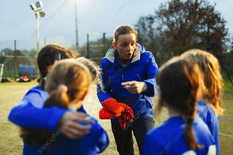 Girls soccer team listening to coach