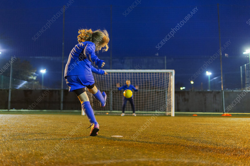 Girl soccer player kicking the ball toward goal