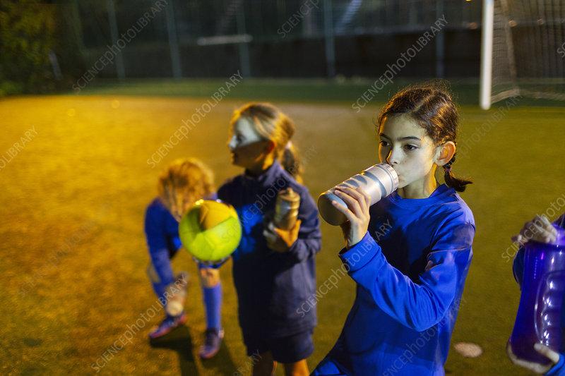 Girl soccer player taking a break, drinking water