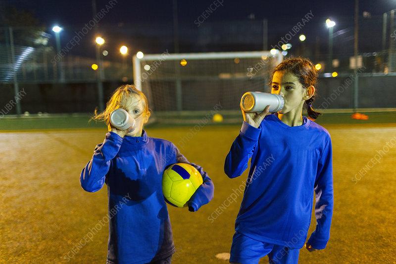 Girl soccer players taking a break, drinking water